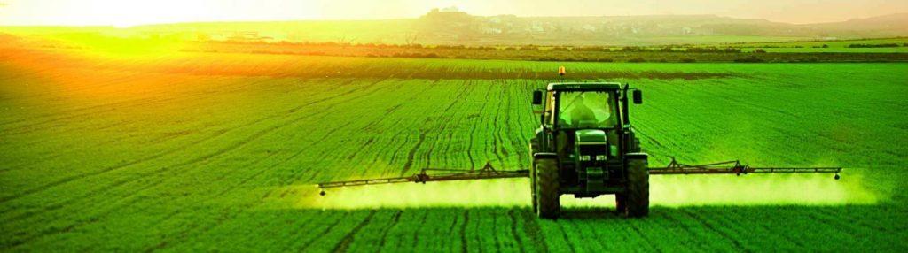 Un tractor esparciendo un líquido en un campo